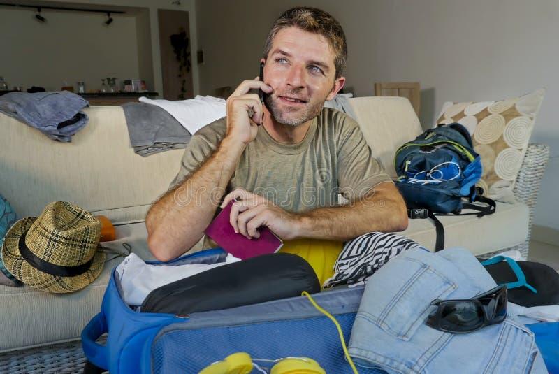 Ung stilig och lycklig man som talar med vännen på för passemballage för mobiltelefon hållande kläder för uppläggning för resväsk royaltyfri fotografi