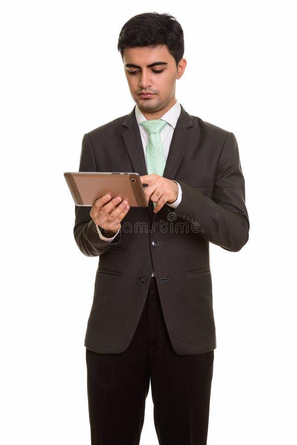 Ung stilig persisk affärsman som använder den digitala minnestavlan arkivfoto