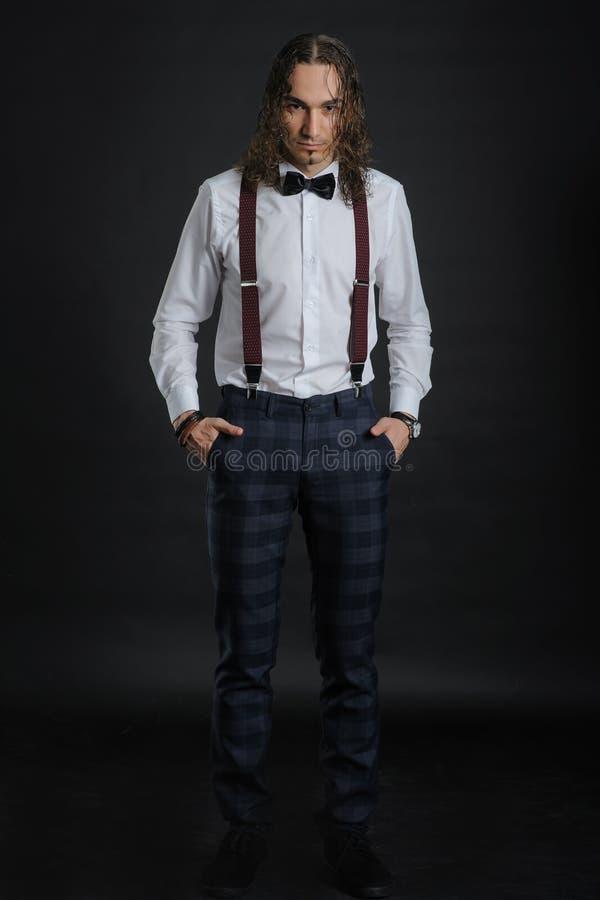 Ung stilig pojke i den vita skjortan med bandet och glases, händer i fack royaltyfri foto