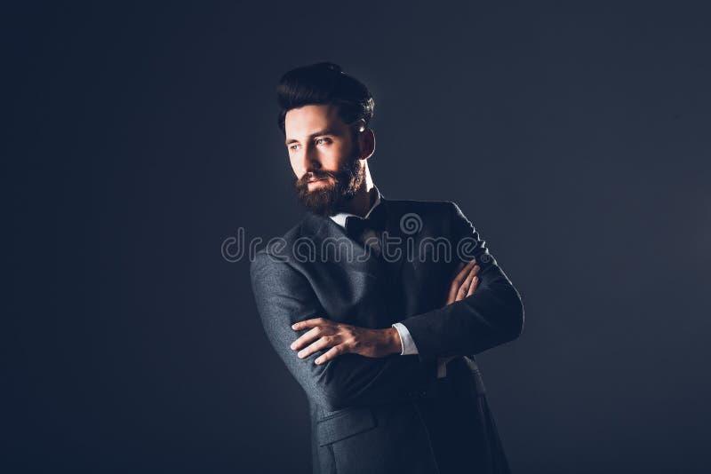 Ung stilig skäggig caucasian man som inomhus poserar Göra perfekt hud och frisyren Bärande elegant omslag, jeans studio royaltyfri fotografi