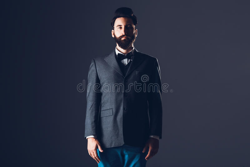Ung stilig skäggig caucasian man som inomhus poserar Göra perfekt hud och frisyren Bärande elegant omslag, jeans studio royaltyfri bild