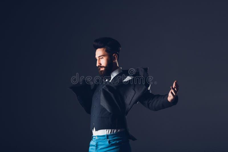 Ung stilig skäggig caucasian man som inomhus poserar Göra perfekt hud och frisyren Bärande elegant omslag, jeans studio arkivbilder