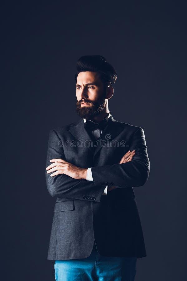 Ung stilig skäggig caucasian man som inomhus poserar Göra perfekt hud och frisyren Bärande elegant omslag, jeans studio arkivfoton