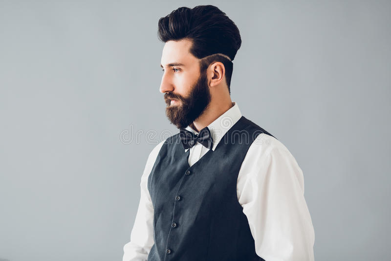 Ung stilig skäggig caucasian man som inomhus poserar Göra perfekt hud och frisyren Bärande väst, vit skjorta, jeans arkivbilder