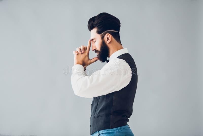 Ung stilig skäggig caucasian man som inomhus poserar Göra perfekt hud och frisyren Bärande väst, vit skjorta, jeans royaltyfri bild