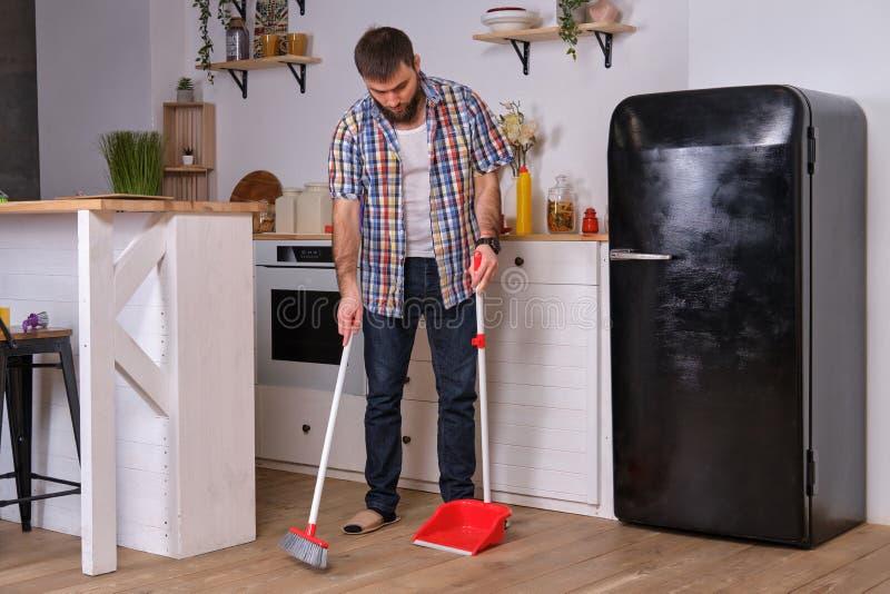 Ung stilig skäggig man i ett kök och att bära en plädskjorta som sopar golvet med en skyffel och en kvast fotografering för bildbyråer