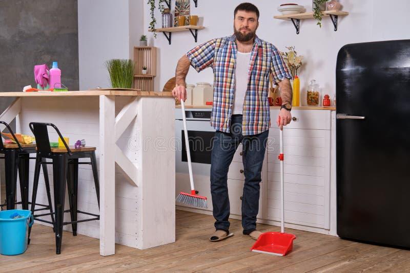 Ung stilig skäggig man i ett kök och att bära en plädskjorta som sopar golvet med en skyffel och en kvast arkivbild