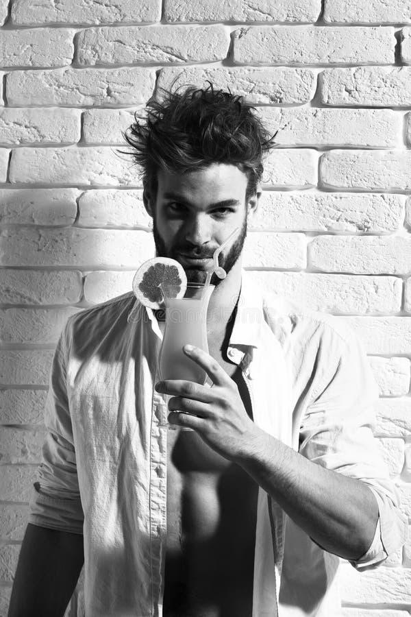 Ung stilig skäggig sexig macho man med det stilfulla skägget i knäppt upp vit skjorta och muskulös kal torso på idrotts- arkivbilder