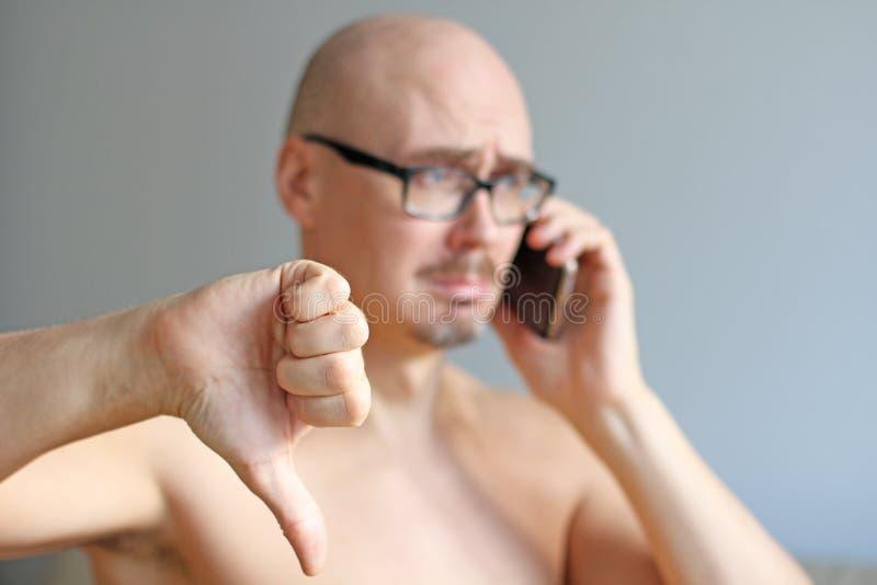 Ung stilig skallig man i svarta exponeringsglas som talar på telefonen closeup isolerad manstående Dåliga nyheter sorgsenhet En m arkivfoton
