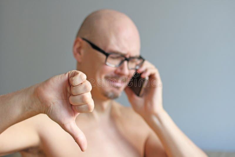 Ung stilig skallig man i svarta exponeringsglas som talar på telefonen closeup isolerad manstående Dåliga nyheter sorgsenhet En m royaltyfria bilder