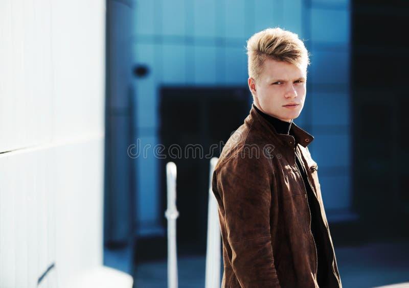 Ung stilig stilfull man i brunt omslag i hösttid som är utomhus- i tillfällig stil arkivfoto