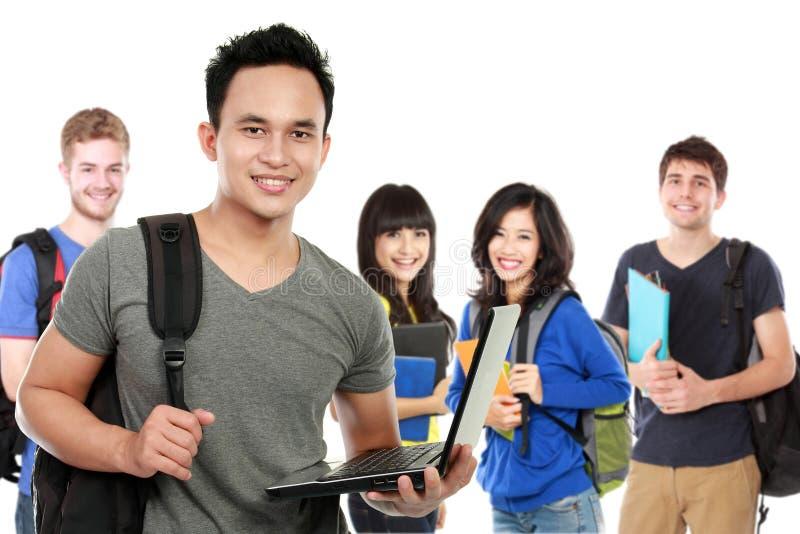 Ung stilig student med bärbara datorn och vänner på bakgrunden royaltyfri foto