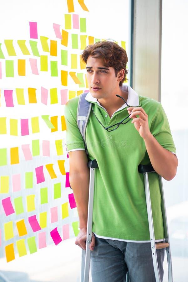 Ung stilig student med kryckor, i att kämpa prioriteter c arkivbild