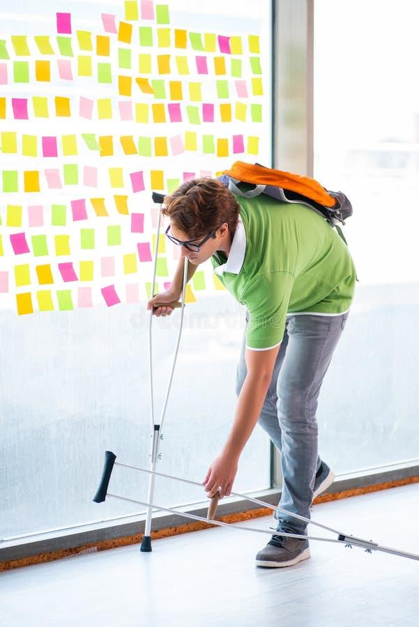 Ung stilig student med kryckor, i att kämpa prioriteter c arkivbilder