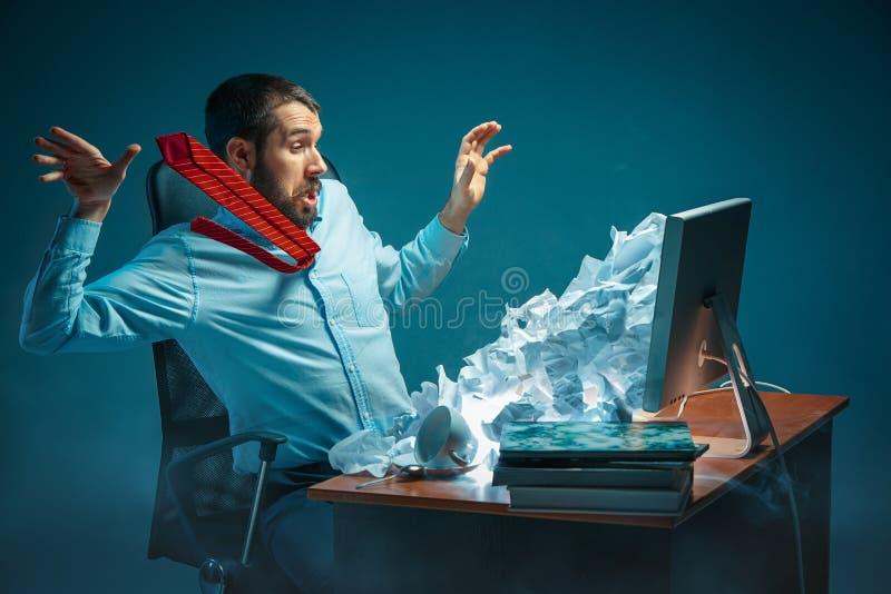 Ung stressad stilig affärsman som arbetar på skrivbordet i moderna kontoret som omkring ropar på bärbar datorskärmen och det är i royaltyfria bilder