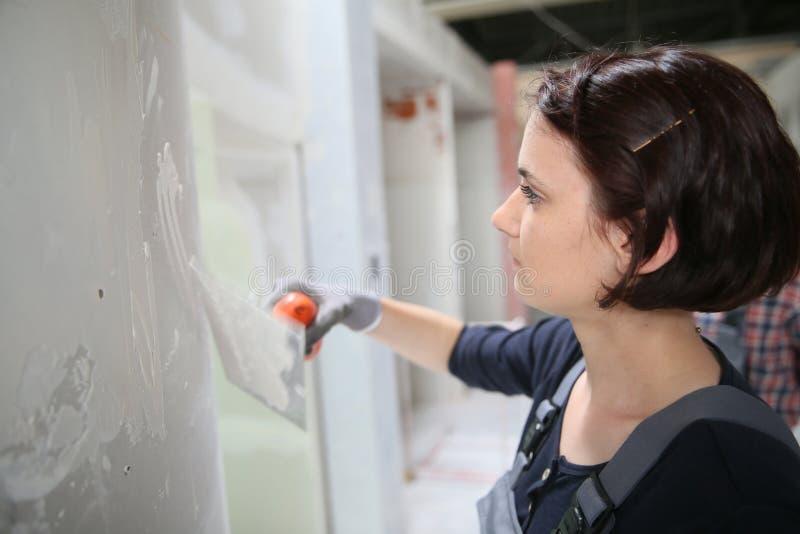 Ung stuckatör som arbetar på väggen royaltyfria foton