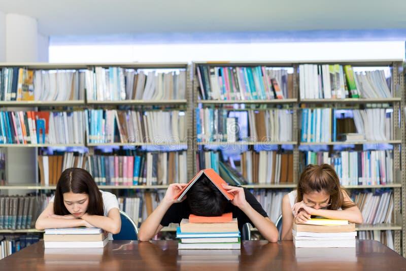 Ung student allvarliga Group Reading Book, hård examen, frågesport, prov som sover huvudvärkbekymmer i universitet för klassrumut arkivfoto