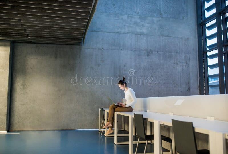 Ung student eller aff?rskvinna som sitter p? skrivbordet i rum i ett arkiv eller ett kontor, genom att anv?nda b?rbara datorn arkivfoton
