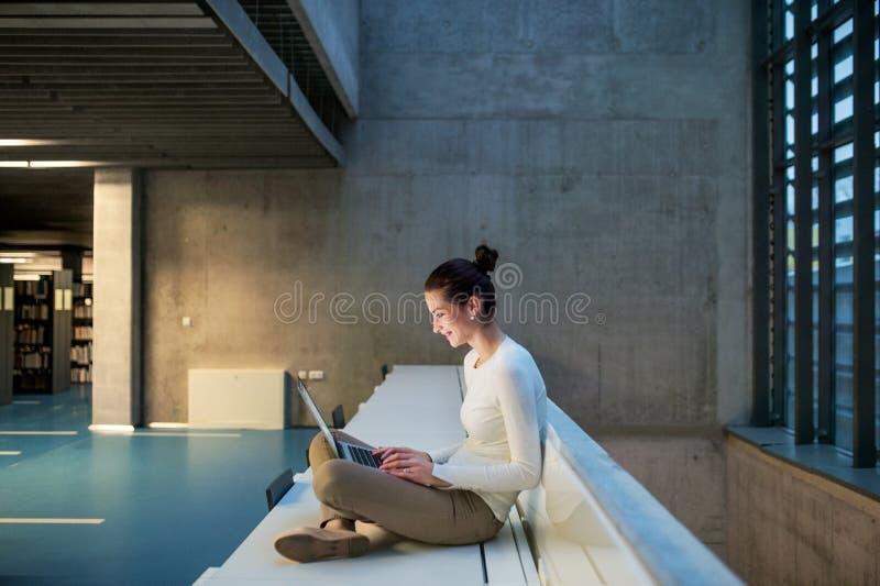 Ung student eller aff?rskvinna som sitter p? skrivbordet i rum i ett arkiv eller ett kontor, genom att anv?nda b?rbara datorn royaltyfri fotografi