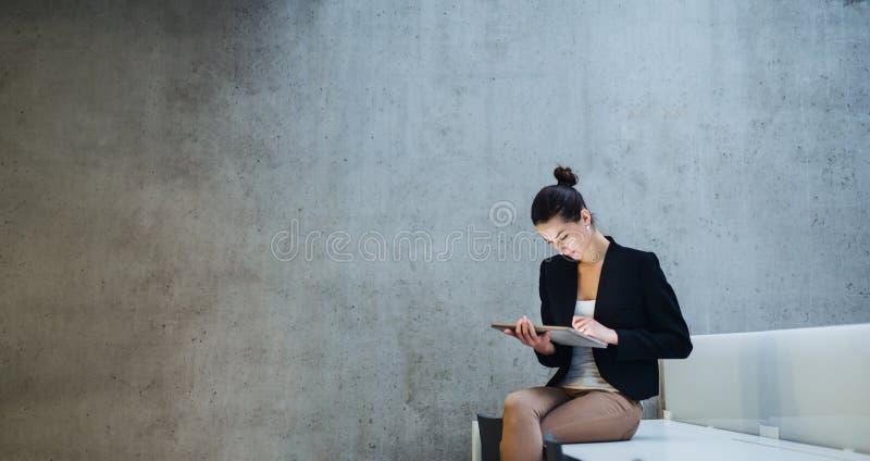 Ung student eller aff?rskvinna som sitter p? skrivbordet i rum i ett arkiv eller ett kontor, genom att anv?nda minnestavlan arkivfoto
