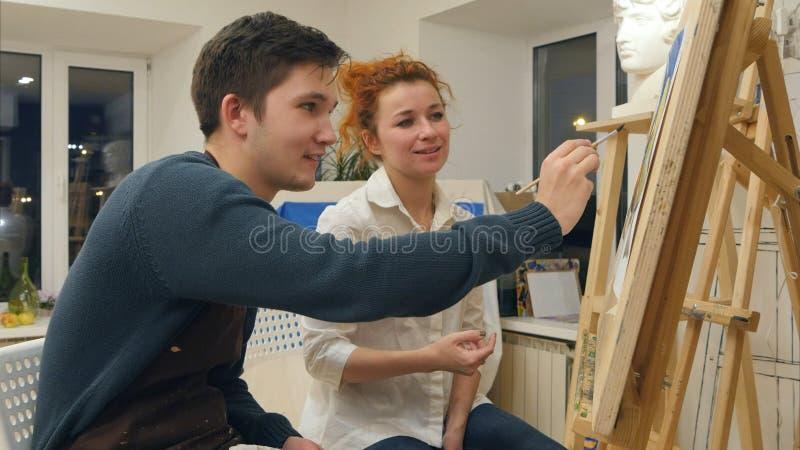 Ung student för kvinnlig konstnärundervisning som ska målas med vattenfärgen royaltyfria bilder