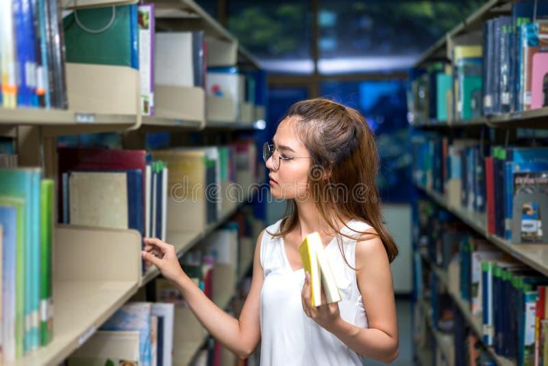 Ung student Girl Finding Book i klassrum arkivfoton