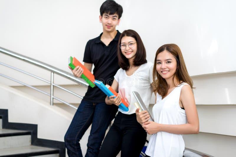 Ung student Group Holding Book och leende för bärbar datordator royaltyfri foto