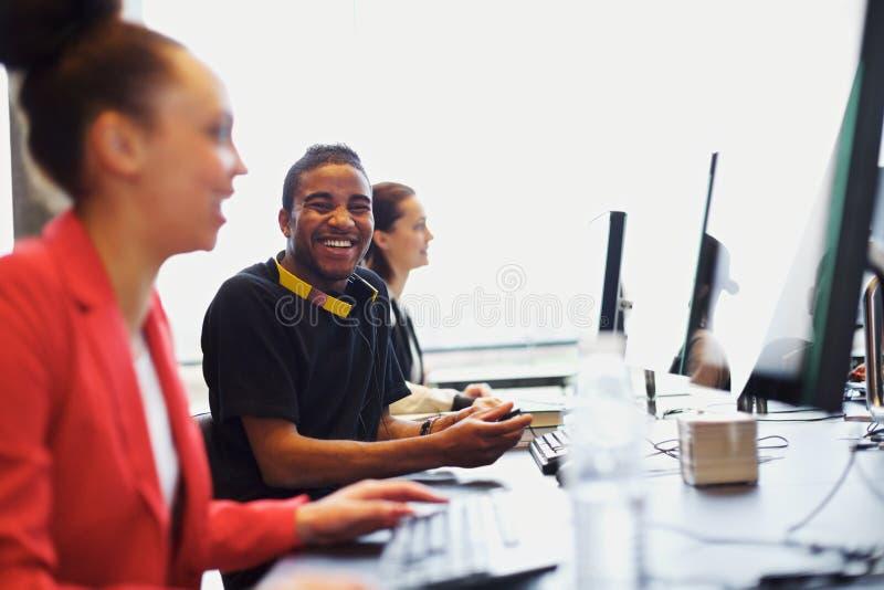 Ung student i grupp med andra studenter som arbetar på datorer royaltyfri bild