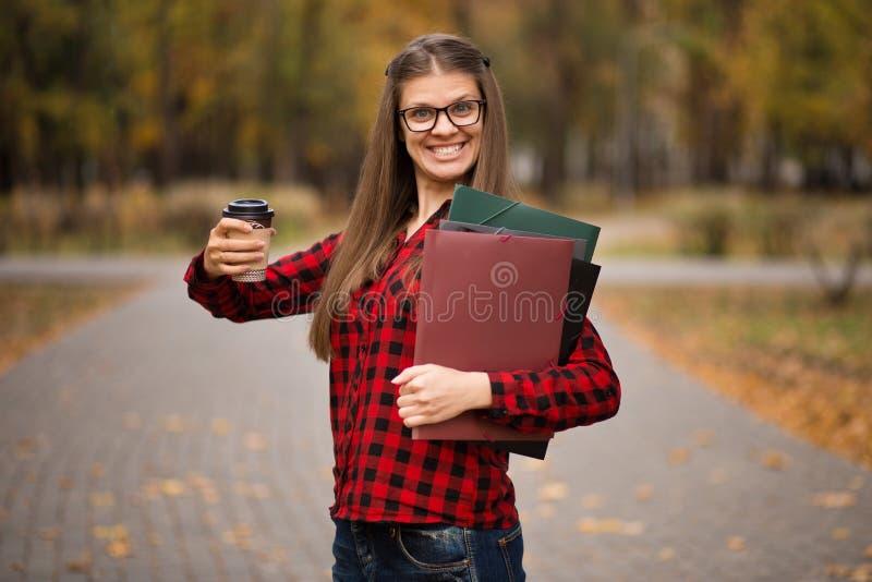Ung student i röd rutig skjorta med koppen kaffe Stående av den härliga unga kvinnan som rymmer mappar royaltyfri foto