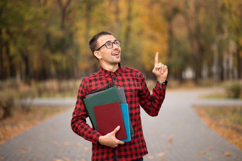 Ung student i röd rutig skjortapunktöverkant Stående av den stiliga unga mannen som rymmer mappar arkivbilder