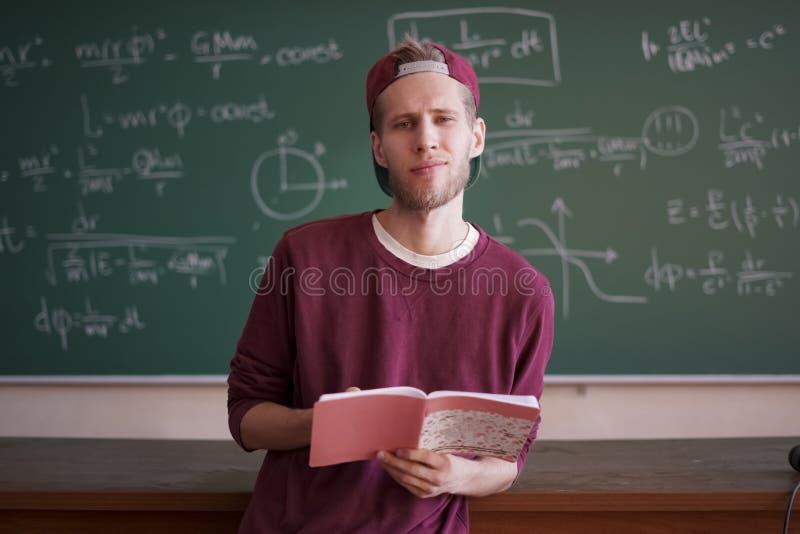 Ung student i tillfälligt anseende nära svart tavla med formler och hållande anteckningsbokkopieringsutrymme royaltyfri bild