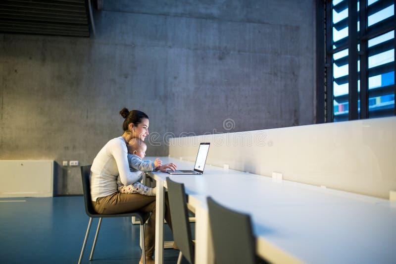 Ung student med att behandla som ett barn att sitta p? skrivbordet i rum i ett arkiv eller ett kontor, genom att anv?nda b?rbara  arkivbild