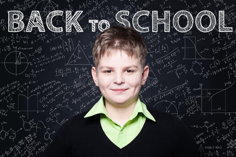 Ung student som ler på den svart tavlan tillbaka bakgrundsskola till arkivfoto