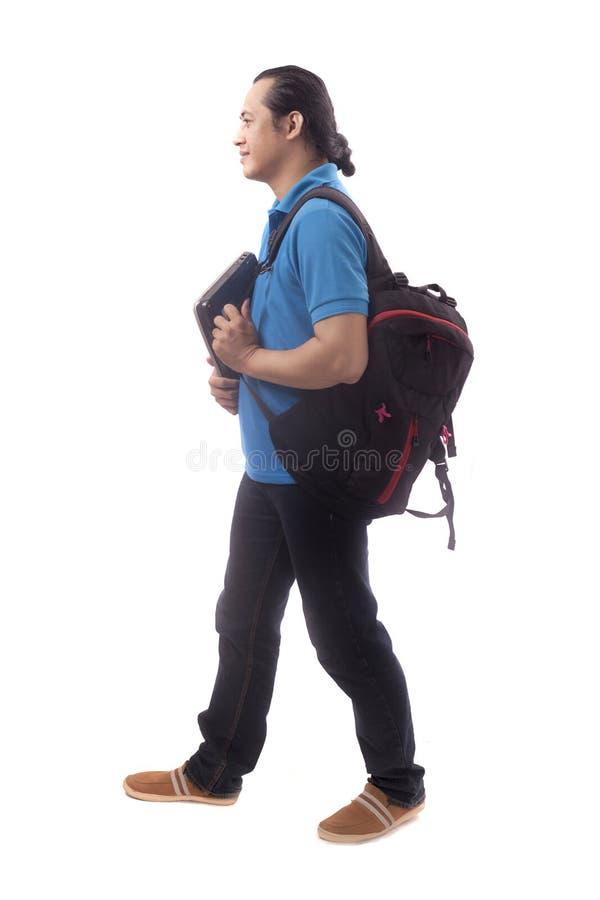 Ung student Walking Forward Isolated p? vit royaltyfri fotografi