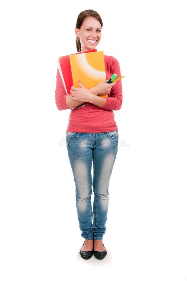 Ung studentflicka med anteckningsböcker som isoleras på vit bakgrund arkivfoto