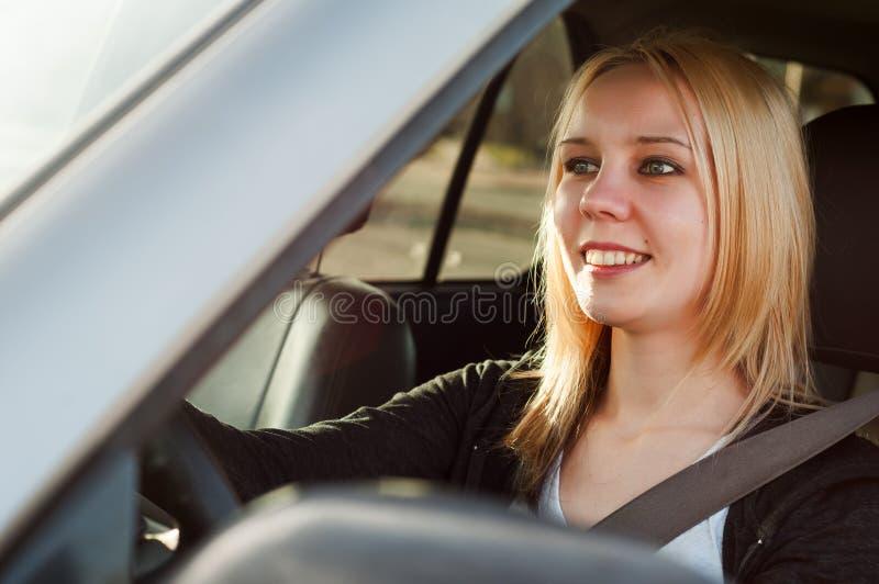 Ung studentflicka som kör en bil royaltyfri fotografi