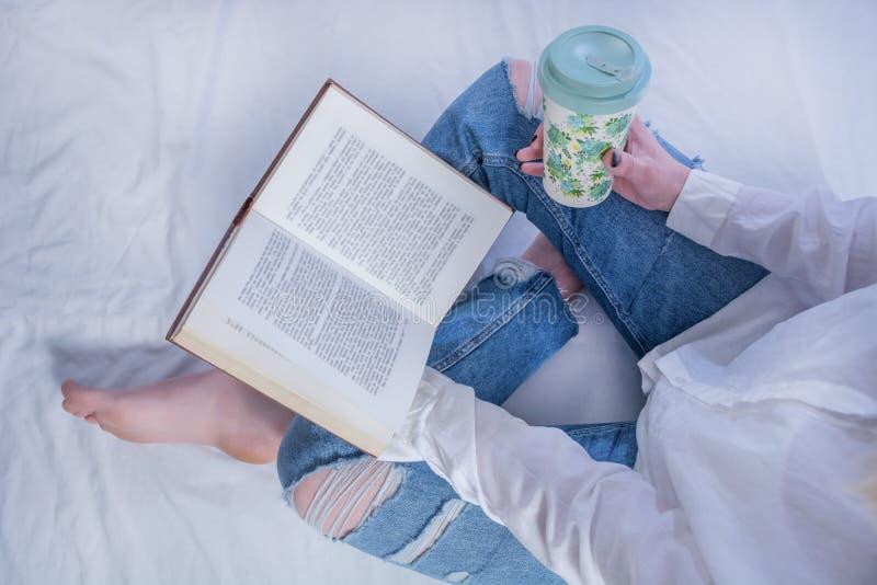 Ung studentflickaläsebok, i hemtrevlig säng och att rymma boken på ben med kal fot och att dricka varmt kaffe i retro kopp arkivbilder