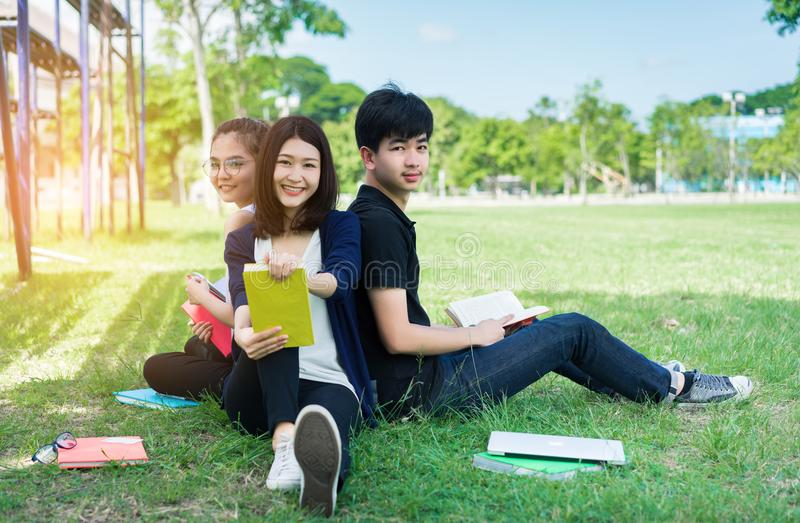 Ung studentgrupp med skolamappar, le för bärbar dator royaltyfri fotografi