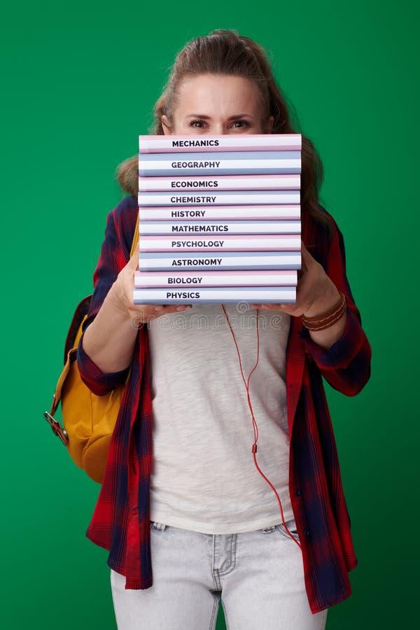 Ung studentkvinna som döljer bak högen av böcker arkivfoto