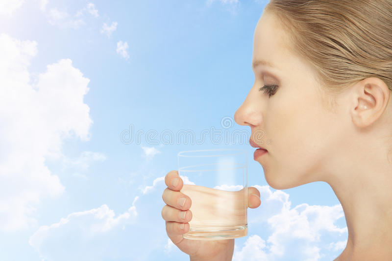 Ung sund kvinna och ett exponeringsglas av clean vatten arkivfoton
