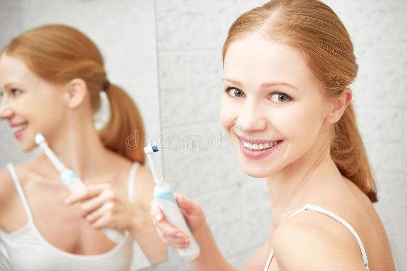 Ung sund kvinna som borstar hennes tänder med en tandborste i slagträ arkivbild