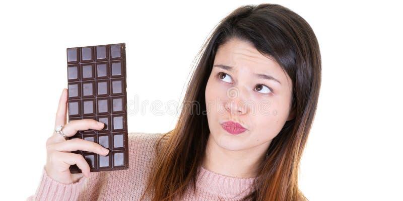 Ung sund kvinna som rymmer några tänkande blickar för choklad lämnade royaltyfri bild