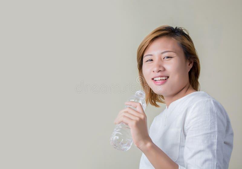 Ung sund kvinnainnehavflaska av vatten och leenden på kameran royaltyfri bild