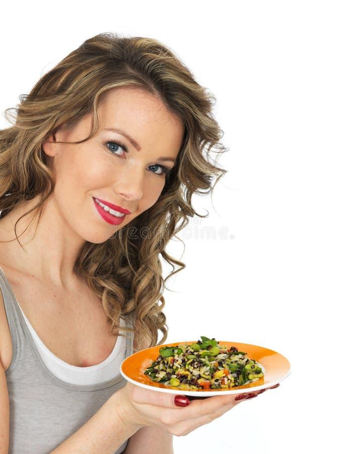 Ung sund kvinnainnehavplatta av sallad för blandad böna och för lösa ris royaltyfri foto