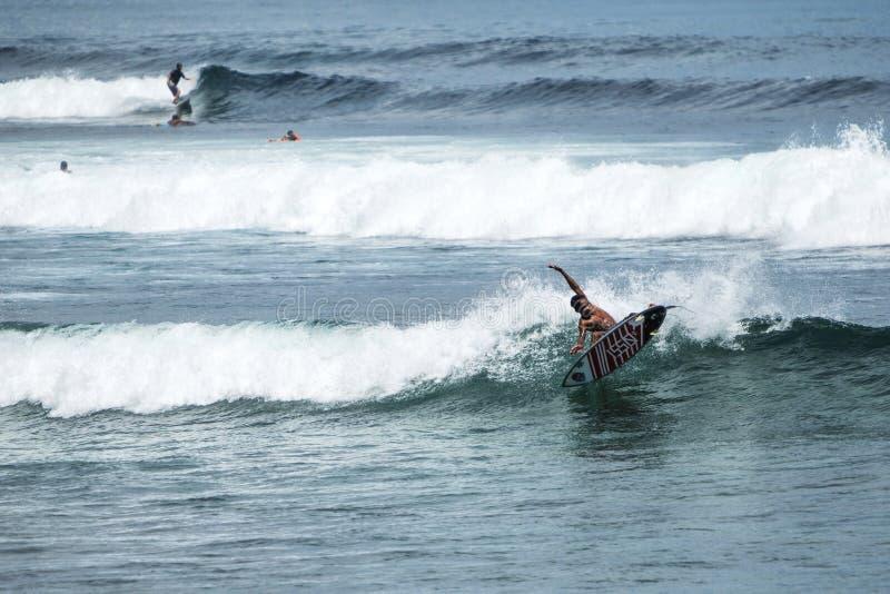 Ung surfare på blå havvåg royaltyfria foton