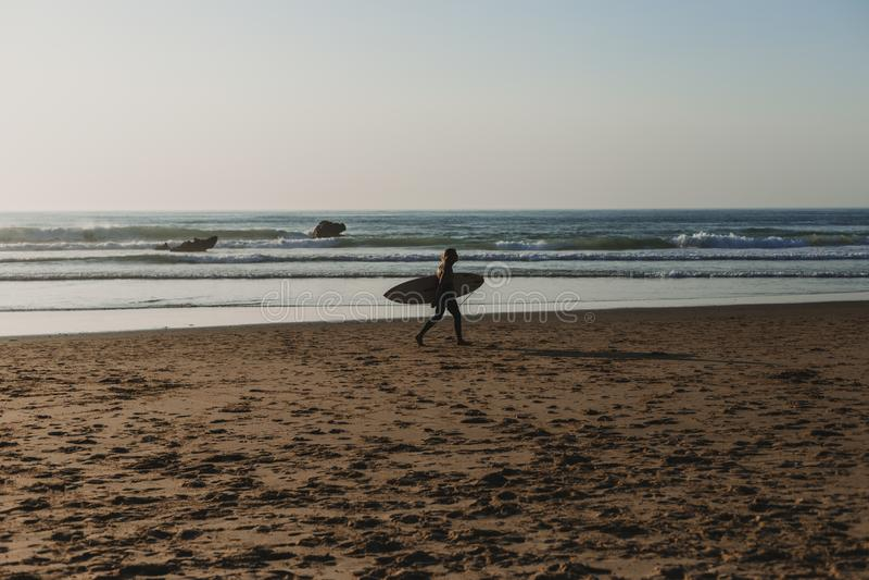 ung surfareman som går av havskusten som rymmer hans bränningtabell Solnedg?ng Sommartid-, sport- och feriebegrepp arkivfoton