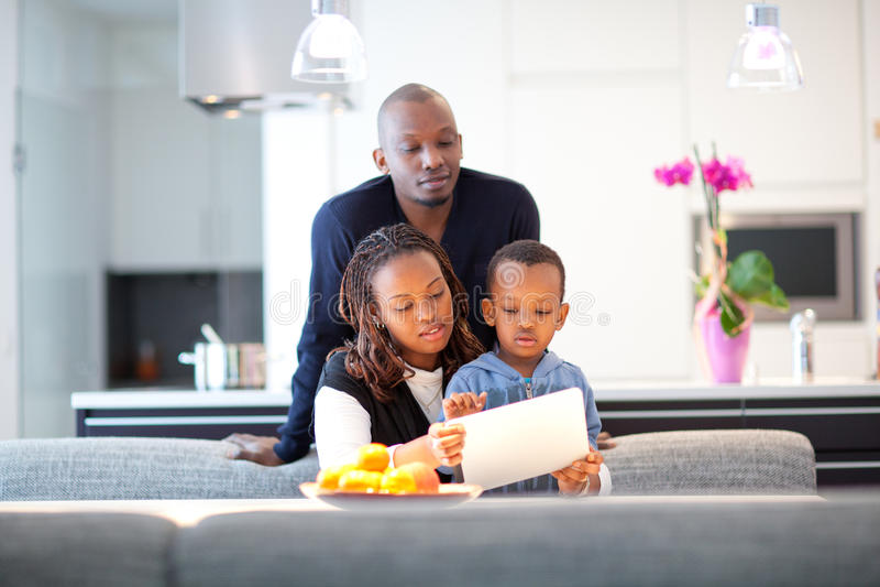 Ung svart familj i nytt modernt kök royaltyfri bild