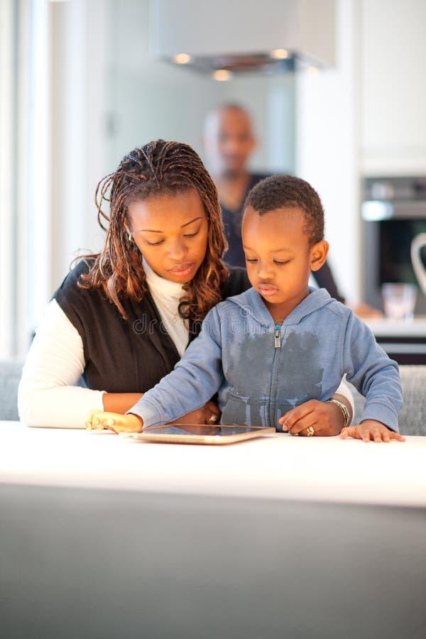 Ung svart familj i nytt modernt kök royaltyfri fotografi