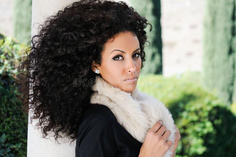 Ung svart kvinna, afro frisyr, i stads- bakgrund royaltyfri bild