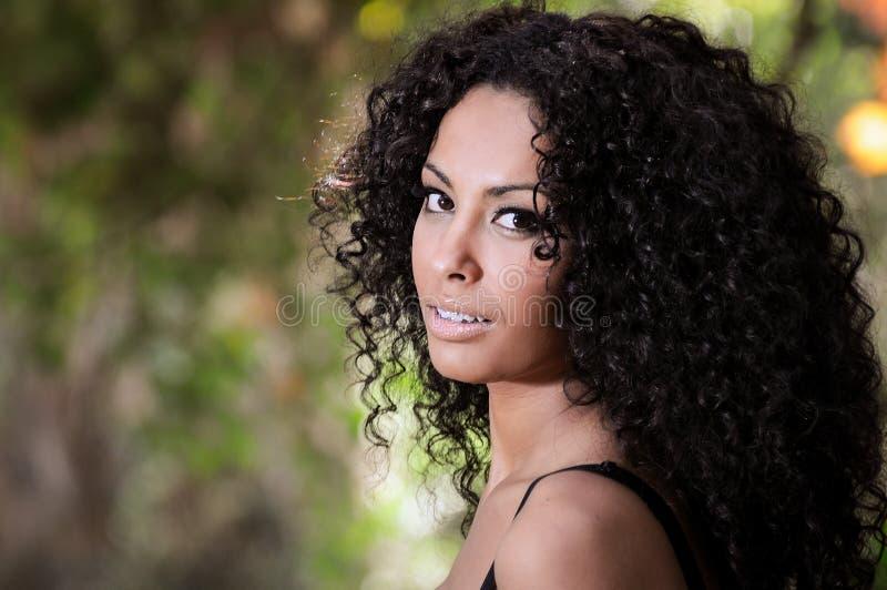 Ung svart kvinna, afro frisyr, i stads- bakgrund fotografering för bildbyråer